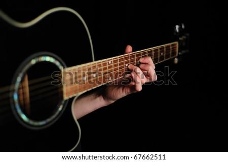 Man's hand striking a chord on a black guitar - stock photo