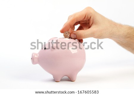 Man's hand throws a penny into piggy bank slot. Pink piggy bank, with coins falling into slot.