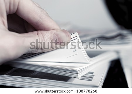 Man's hand turned over a stack of magazines close up - stock photo