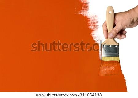 Man's hand using paintbrush with orange paint on wall - stock photo