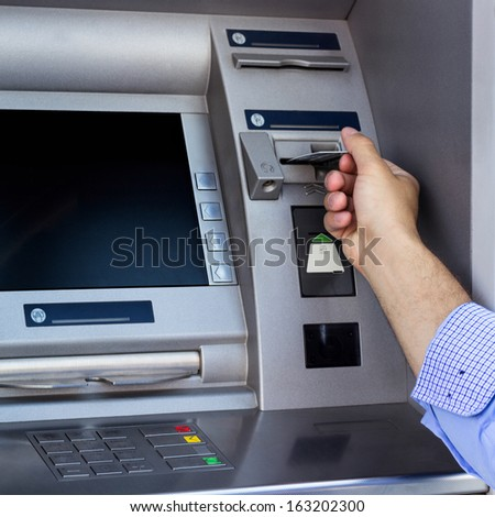 Man's hand using the ATM