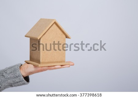 Man's hand wearing warm gray sweater holding little wooden house at gray studio background, close up, mock up, copy space.