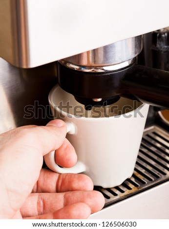 Man's hand with a cup of fresh coffee with foam - stock photo