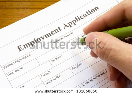 "man's hand with a fountain pen over blank ""application for employment"""