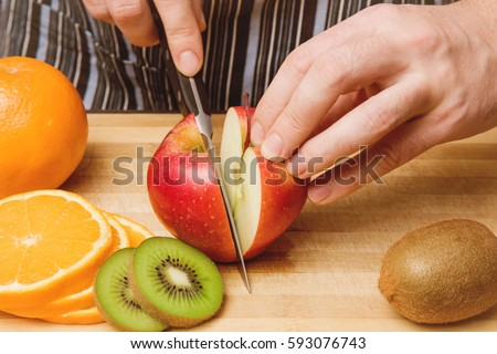 Man's hand with a knife cuts the apple on the wooden board in the kitchen. Healthy eating and lifestyle.