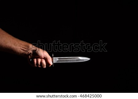 Man's hand with a knife in the dark