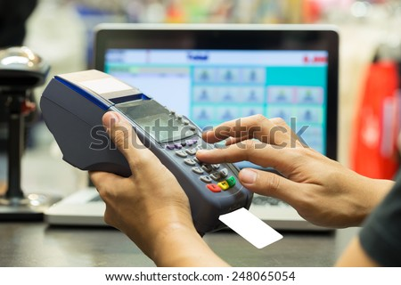 man's hand with credit card swipe through terminal for sale in store - stock photo