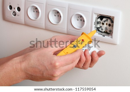 Man's hand with detector checking voltage in power socket - stock photo