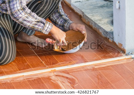 Man's hand with grout trowel while working on ceramic tile