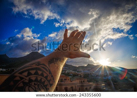 Man's hand with tattoo over town and blue sky with fluffy clouds - stock photo