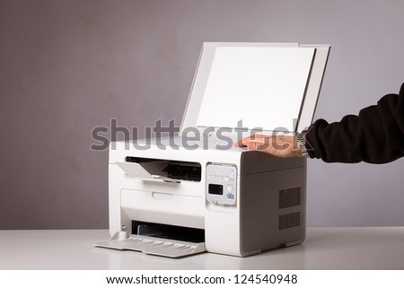 Man's hand with working copier - stock photo