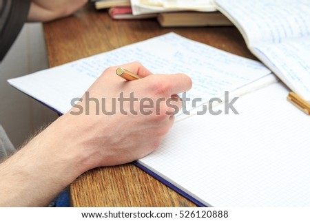 Man's hand writing letters in his notebook