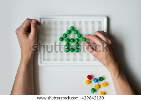 Man's hands and children's mosaic. Green House.  - stock photo
