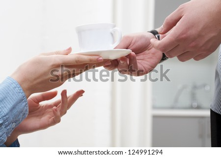 Man�¢??s hands and woman�¢??s hands holding white cup - stock photo