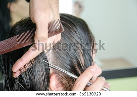 Man's hands cut and comb female dark brown hair in a beauty salon with mirrors