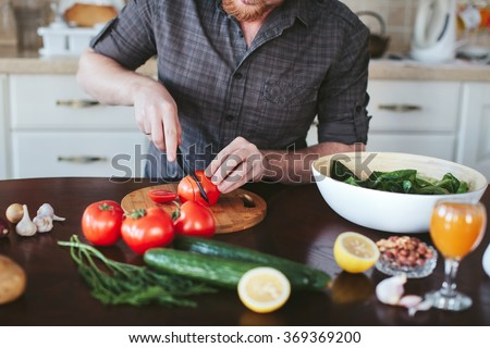 man's hands cut tomato on the board for a vegetarian salad - stock photo