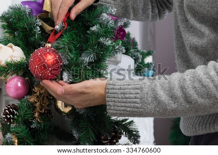 Man's hands decorating mantel with christmas garland, baubles and pine cones - stock photo