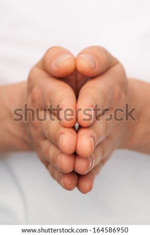 Man's hands folded over white body background. - stock photo