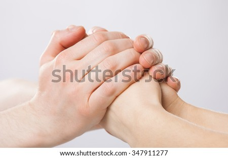 Man's hands gently holding woman's hands - closeup shot