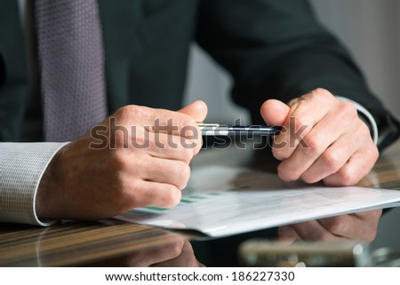 Man's hands holding a black pen in both arms in a thinking gesture during a meeting or negotiation - stock photo