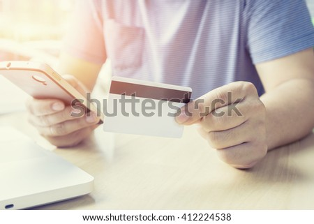 Man's hands holding a credit card and using smart phone and laptop,Online payment shopping concept,Internet Theft ,selective focus and vintage colorlaptop.Online shopping,vintage color,selective focus - stock photo