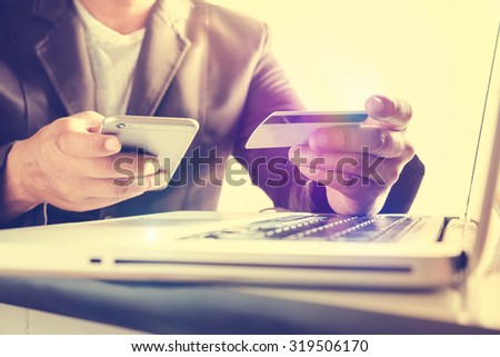 Man's hands holding a credit card and using smart phone for online shopping,retro effect. - stock photo