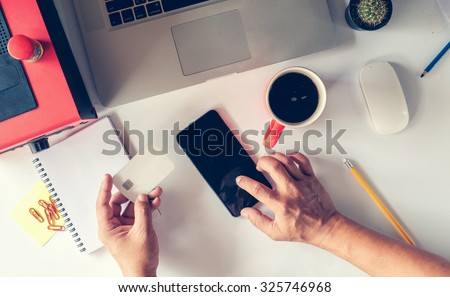 man's hands holding a credit card and using smart phone for online shopping.Vintage or retro color effect. - stock photo