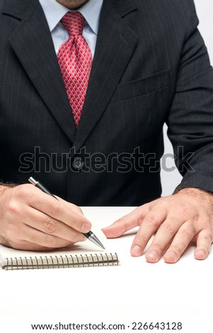 Man's Hands Holding A Pen Writing A Text - stock photo