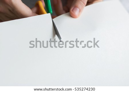 Man's hands holding and cutting white paper with colored scissors - from top to the bottom. Playing with paper, being creative, Closeup
