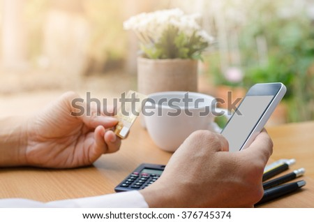 Man's hands holding mobile smartphone and credit card on wooden table with cup of coffee, internet banking, online trading concept, e commerce concept. - stock photo