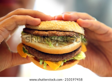 man's hands, holding onto a burger - stock photo
