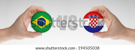 Man's hands holding styrofoam balls with Brazilian and Croatian flag against the white background. - stock photo