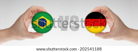 Man's hands holding styrofoam balls with Brazilian and German flag against the white background. - stock photo