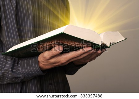 Man's hands holds Koran - holy book of muslims, shallow depth of field. - stock photo