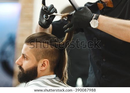 Man's hands in black gloves wearing watch doing a haircut with scissors for man with dark long hair and beard at barber shop, close up portrait, copy space.