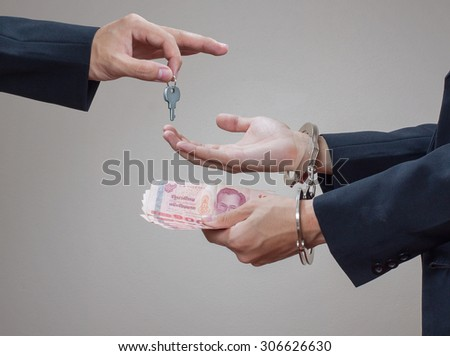 Man's hands in handcuffs and money in his palms - stock photo