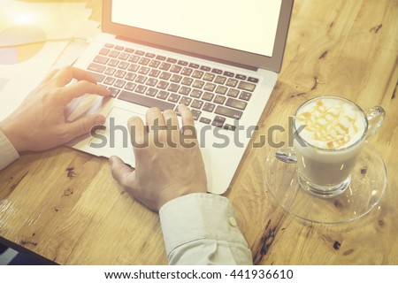 man's hands keyboarding on net-book while sitting at the wooden table in cafe,student working laptop computer with copy space screen with a cup of coffe ,male freelancer,vintage color.,selective focus - stock photo
