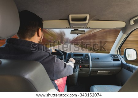 Man's hands of a driver on steering wheel of a car on road