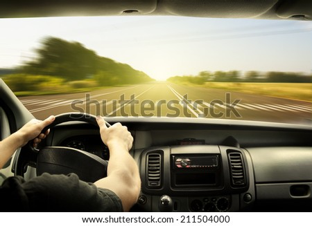 Man's hands of a driver on steering wheel of a minivan car on asphalt road in morning  - stock photo