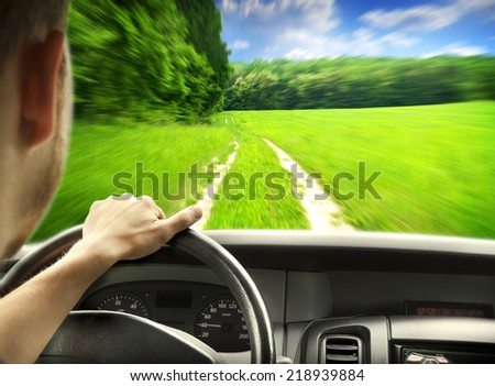 Man's hands of a driver on steering wheel of a minivan car on country road - stock photo