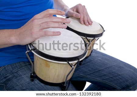 man's hands playing bongos on knees, whilst seated - stock photo