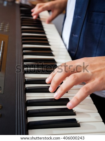 Man's Hands Playing Piano In Recording Studio