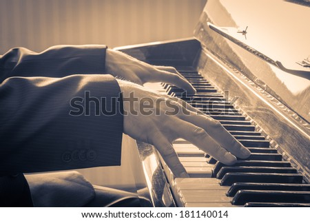 Man's hands playing the Piano.  Retro Style. Warm color toned - stock photo