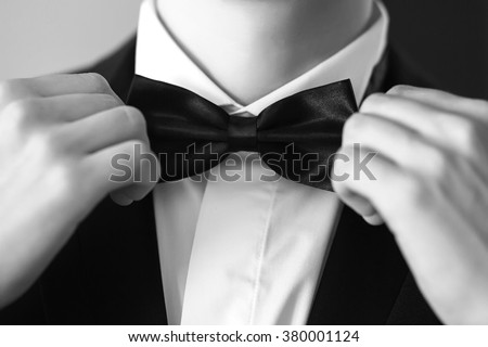 Man's hands touches bow-tie on a suit or tuxedo black and white