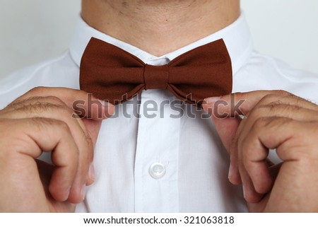 Man's hands touching bow-tie - stock photo