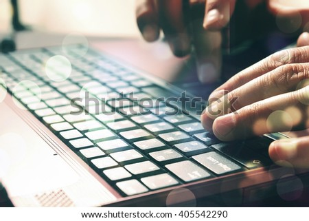 Man's hands typing on laptop keyboard. Double expo - stock photo