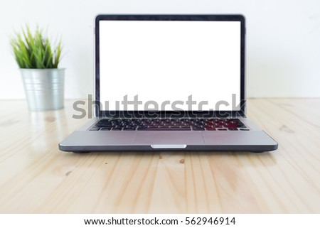 Man's hands using laptop with blank screen on desk in home