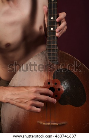 Man's hands with folk musical instrument domra