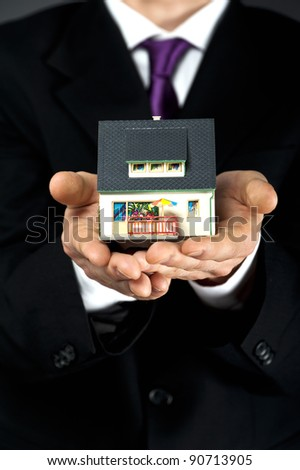 man's hands with house on it