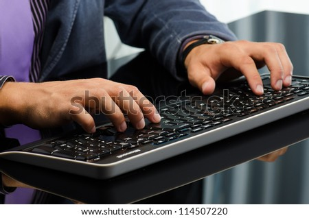Man's hands working on computer keyboard